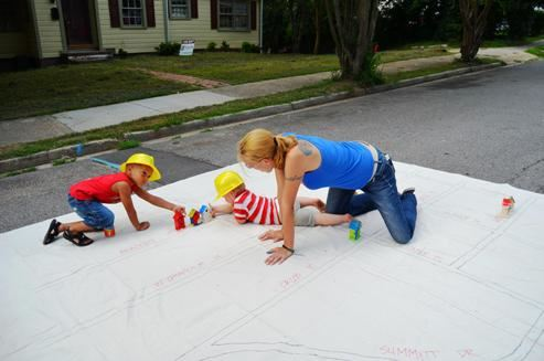 Resident with two young children painting on a large canvas